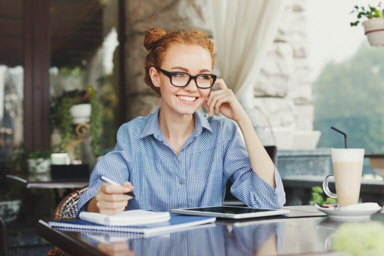 Young redhead girl making notes in a notebook